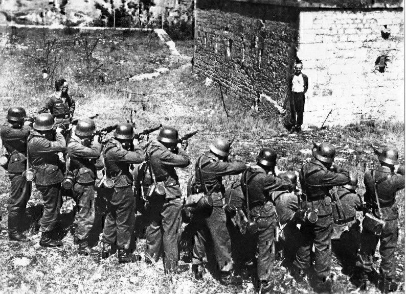 French Resistance member Georges Blind smiling in front of a German execution squad. October 1944. It was a mock execution intended to make him talk. (Photo: Nat'l Archives)
